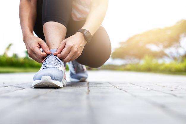 Giovane donna che lega le scarpe da jogging.