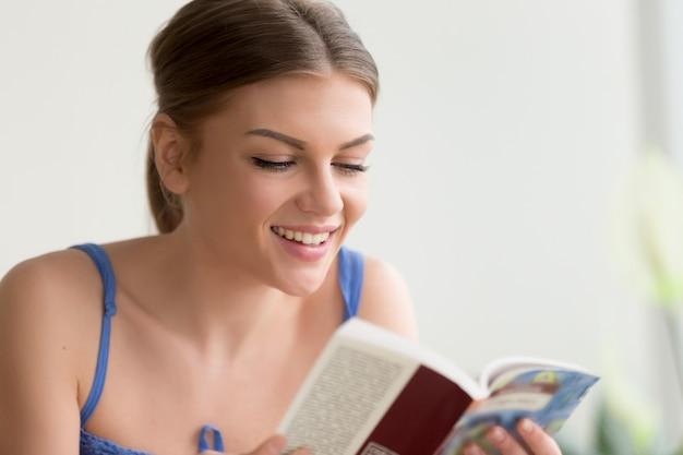 Giovane donna che legge con interesse nuovo libro