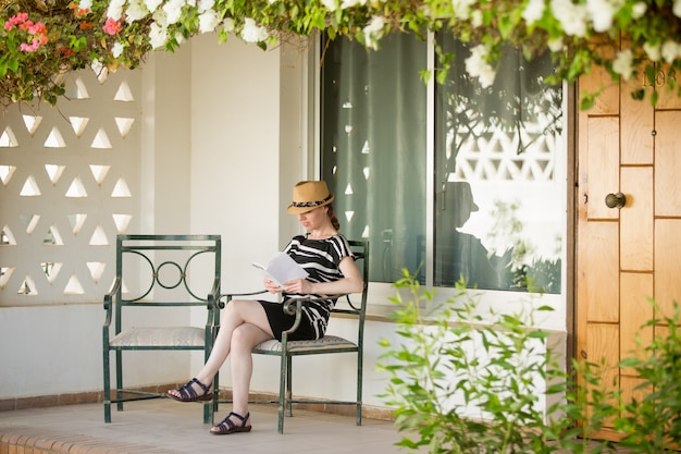 Giovane donna che legge sulla veranda