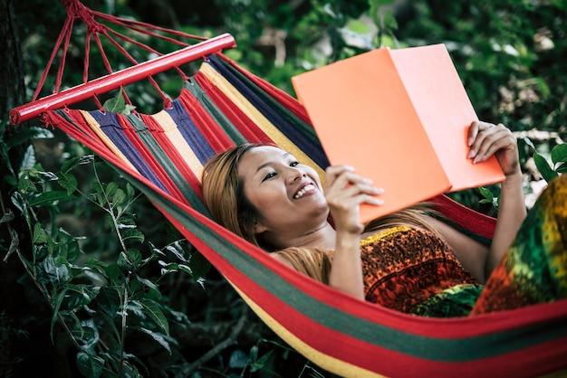 Giovane donna che legge un libro che si trova in un'amaca