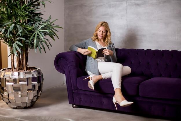 Giovane donna che legge un libro e che si siede sul sofà comodo a casa