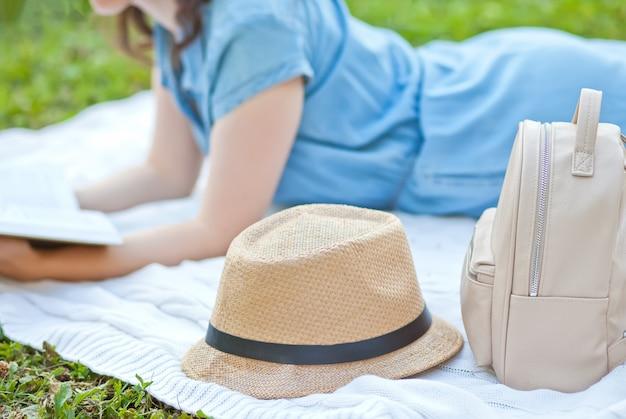 Giovane donna che legge un libro nel parco cittadino.