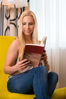 Giovane donna che legge un libro nella camera d'albergo