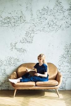 Giovane donna che legge un libro su un divano