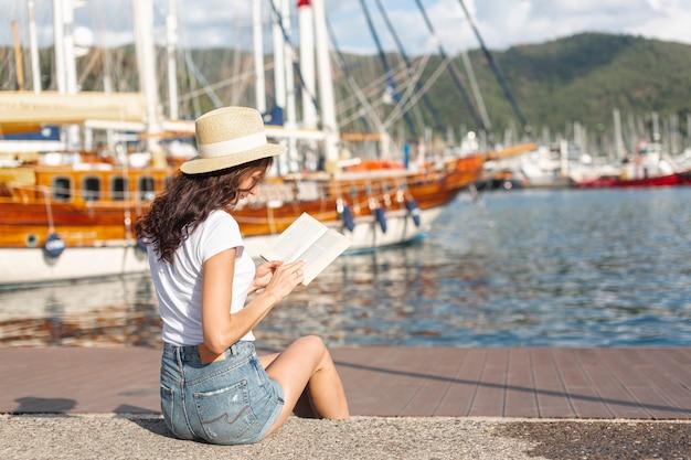 Giovane donna che legge un libro sul porto