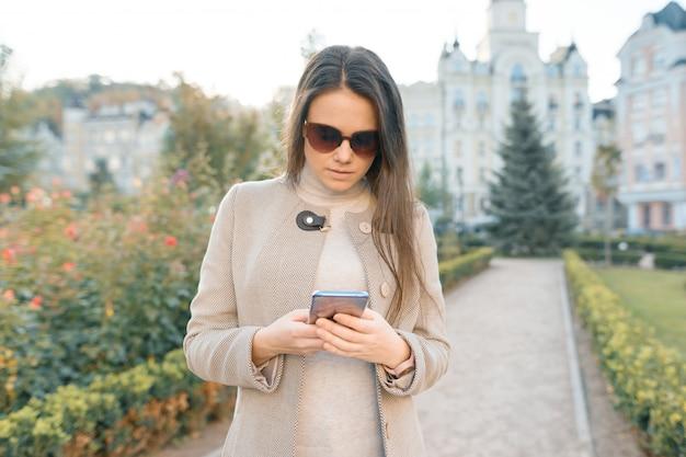 Giovane donna che manda un sms sullo smart phone