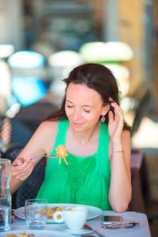 Giovane donna che mangia gli spaghetti al caffè all'aperto sulla vacanza italiana
