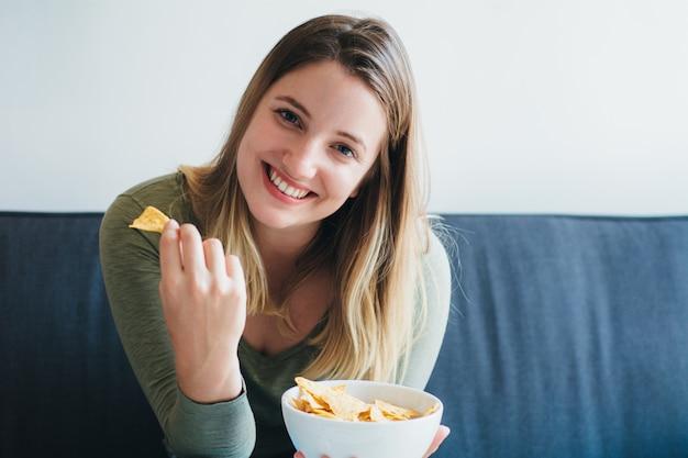 Giovane donna che mangia gli spuntini sul divano