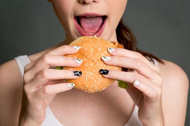 Giovane donna che mangia hamburger su sfondo grigio