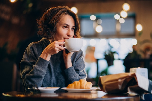 Giovane donna che mangia i croissant ad un caffè