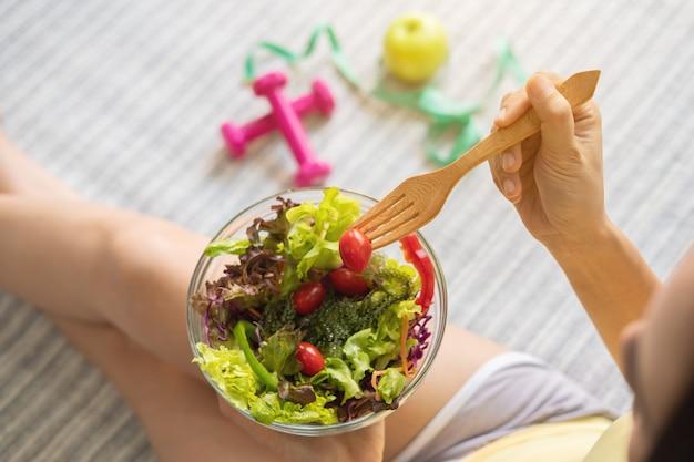 Giovane donna che mangia insalata sana casalinga a casa, stile di vita sano, concetto di dieta