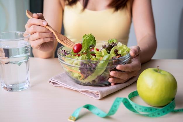 Giovane donna che mangia insalata sana casalinga a casa
