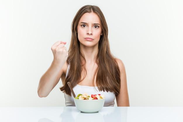 Giovane donna che mangia la ciotola di frutta che mostra pugno alla macchina fotografica