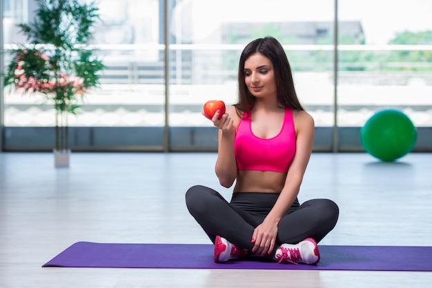 Giovane donna che mangia mela rossa nel concetto di salute