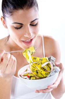 Giovane donna che mangia metro del sarto con la forcella