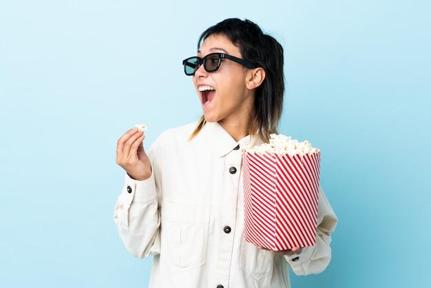 Giovane donna che mangia popcorn sopra la parete isolata
