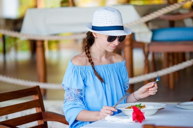 Giovane donna che mangia prima colazione al caffè all'aperto sulle vacanze estive