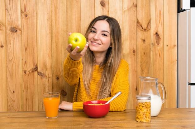 Giovane donna che mangia prima colazione in una cucina con una mela