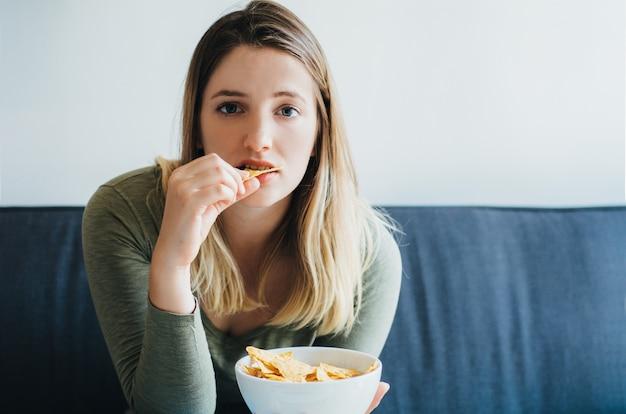 Giovane donna che mangia snack sul divano