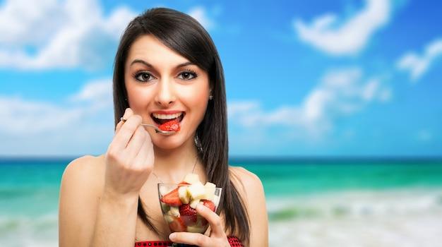 Giovane donna che mangia un cocktail di frutta all'aperto