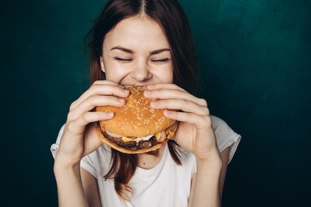 Giovane donna che mangia un hamburger