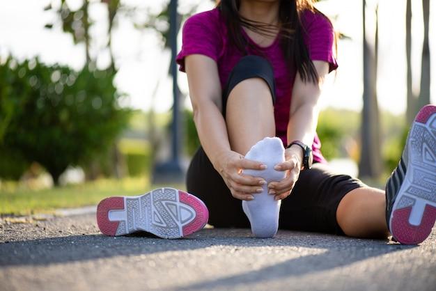 Giovane donna che massaggia il suo piede doloroso mentre si esercita