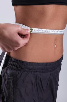 Giovane donna che misura la sua vita con la misura di nastro