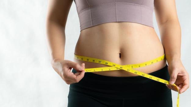 Giovane donna che misura la sua vita della pancia con nastro adesivo di misura, concetto di stile di vita di dieta della donna
