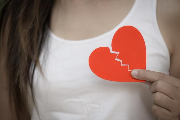 Giovane donna che mostra cuore di carta strappato rosso. cuore spezzato