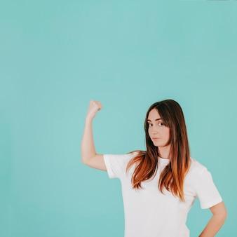 Giovane donna che mostra i muscoli