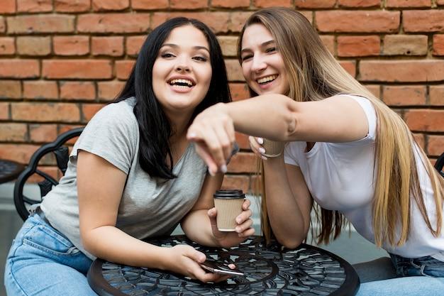 Giovane donna che mostra qualcosa alla sua amica