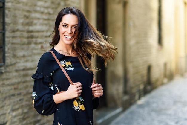 Giovane donna che muove i suoi lunghi capelli in fondo urbano.