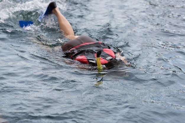 Giovane donna che nuota sott'acqua in piscina indossando boccaglio e scarpe da sub (pantofole, scarpe da sub).