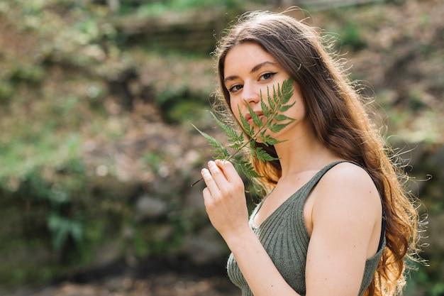 Giovane donna che odora su una foglia nella foresta