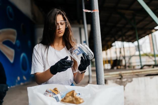 Giovane donna che ordina immondizia. concetto di riciclaggio. zero sprechi
