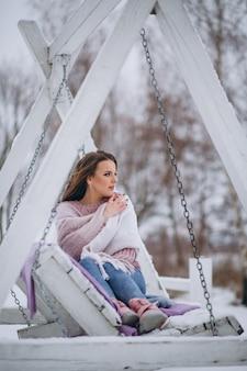 Giovane donna che oscilla in un parco di inverno