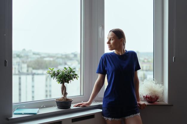 Giovane donna che osserva attraverso la finestra la città