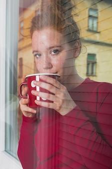Giovane donna che osserva attraverso la finestra