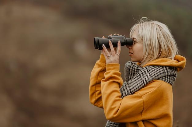 Giovane donna che osserva con il binocolo