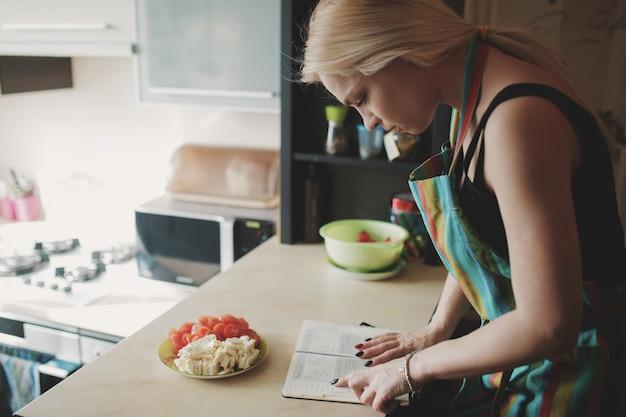 Giovane donna che osserva in su in un libro di ricette