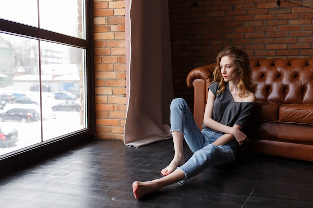 Giovane donna che osserva nella finestra in un appartamento loft.