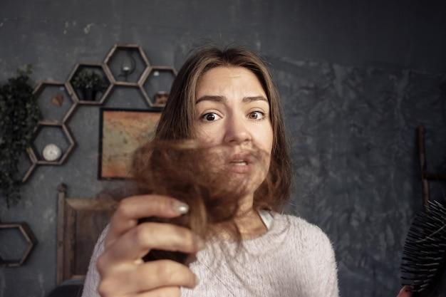 Giovane donna che osserva sul pettine con capelli, orrore e collera, problemi di capelli