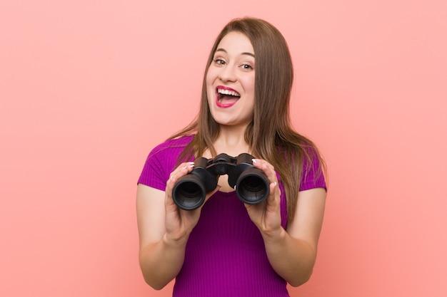 Giovane donna che osserva tramite il binocolo