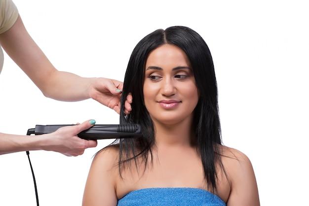 Giovane donna che ottiene il raddrizzatore dei capelli isolato