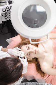 Giovane donna che ottiene l'iniezione dei riempitori di dermall