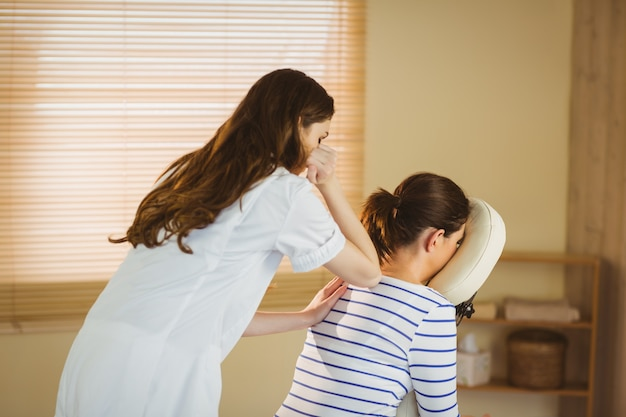Giovane donna che ottiene massaggio in poltrona