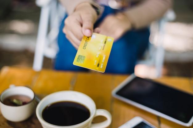 Giovane donna che paga per il caffè dalla carta di credito