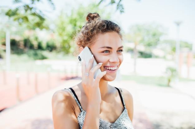 Giovane donna che parla al telefono cellulare in strada