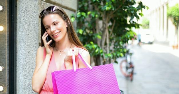 Giovane donna che parla al telefono durante lo shopping in una città