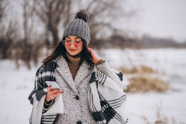Giovane donna che parla al telefono fuori nel parco di inverno